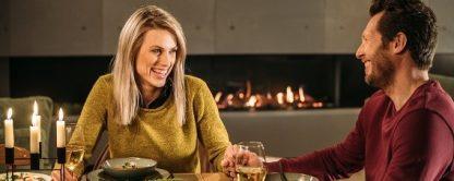 Paar am Tisch vor Elektrokamin